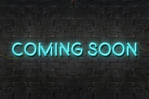 """COMING SOON"" neon sign shining on black brick wall"