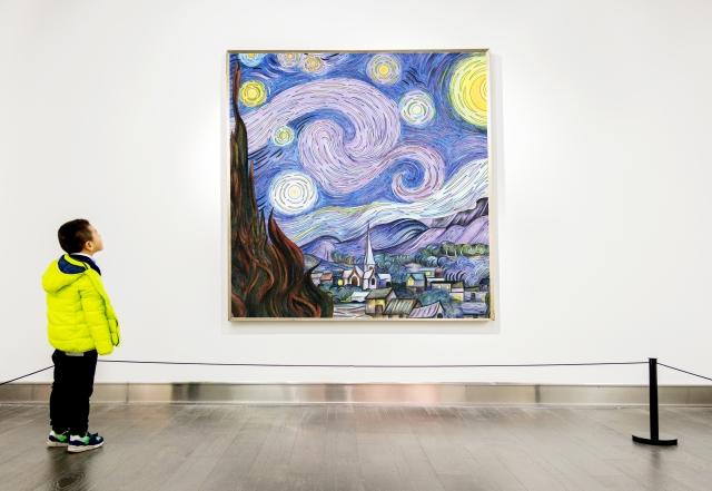 Asian boy looking at artwork
